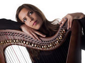Beautiful brunette leaning on her classical harp — Стоковое фото