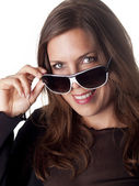 Beautiful smiling brunette looking over her sunglasses — Stock Photo