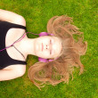 Beautiful Teenage Girl with headphones lying on her back in the grass — Stock Photo #50299249