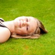 Beautiful smiling teenage girl lying on her back in the green grass — Stock Photo #50299251
