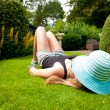 Teenage Girl with a hat covering her face lying on her back in the grass — Stock Photo