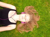 Beautiful Teenage Girl with headphones lying on her back in the grass — Stock Photo