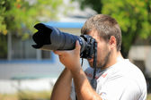 Photographer with telephoto lens — Stock Photo