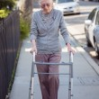 Senior woman walking with walker — Stock Photo