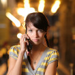 Cute teenage girl with cell phone on brightly lit street — Stock Photo