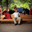 Man on bench, surrounded by sexy woman — Stock Photo