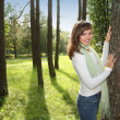 Happy woman leaning on tree — Stock Photo