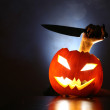 Hand with knife in Jack-o-lantern — Stock Photo #32421011