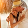Maturecouple kissing on tropical beach — Stock Photo