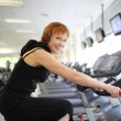 Woman exercising on bike — Stock Photo #32423283