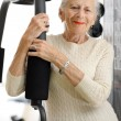 Stock Photo: Senior woman with fitness machine