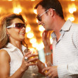 Adult couple enjoying nightlife with glasses of champagne — Stock Photo