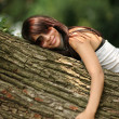 Happy beautiful girl hugging big tree in park — Stok fotoğraf