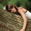 Happy beautiful girl hugging big tree in park — Стоковое фото