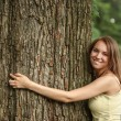 Happy beautiful girl hugging big tree in park — Foto de Stock   #32424013