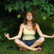 Beautiful young woman relaxing in park in yoga pose — Stock Photo