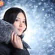 Young woman over falling snow background — Stock Photo