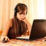 Teenage girl using laptop computer at home — Stock Photo