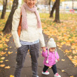Mother with child in yellow autumn city. — Stock Photo