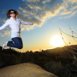 Happy young woman jumping in park at sunset — Stock Photo