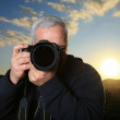 Nature photographer taking photo at sunset — Stock Photo #32425817