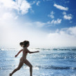 Young woman running along ocean — Stock Photo #32425875