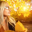 Woman with bunch of yellow autumn leaves — ストック写真