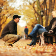 Man talking to hot blond woman in autumn park. — Stock Photo #32426211