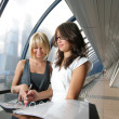 Two businesswomen looking into papers in futuristic interior — Stock Photo