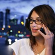 Beautiful young woman talking on mobile phone in night city — Stock Photo