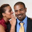 Woman wispering in husband's ear — Stock Photo