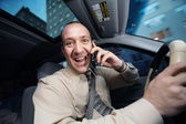 Businessman driving in car and talking on cell phone — Stock Photo