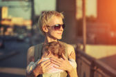 Mother carrying baby — Stock Photo
