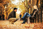 Man talking to hot blond woman in autumn park. — Stock Photo