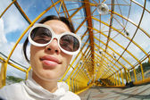Wide angle portrait of a young woman in sunglasses — Stock Photo