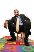 Big businessman sitting on small chair — Stock Photo