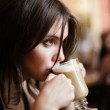 Beautiful young girl sipping coffee lattee. — Stock Photo