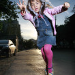 Little girl jumping on the street — Stock Photo