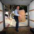 Man  carrying boxes into empty truck. — Stock Photo