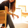 Beautiful young woman sitting in chair — Stockfoto