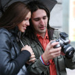 Young couple under umbrella looking at camera — Stock Photo