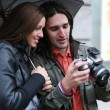 Stock Photo: Young couple under umbrella looking at camera