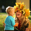 Stock Photo: Mother playing with son in an autumn park.