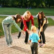 Three women playing with a small boy. — Foto Stock