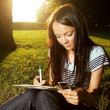Beautiful young female student studying outdoors — Stok fotoğraf