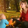 Mother playing with son in an autumn park. — Stockfoto