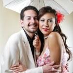 Happy smiling young couple under umbrella — Stock Photo #32907441