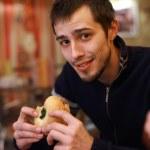 Young man eating burger — Stok fotoğraf