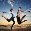 Happy girls jumping at the beach at sunset — Stock Photo