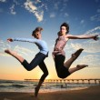 Happy girls jumping at the beach at sunset — Stok fotoğraf